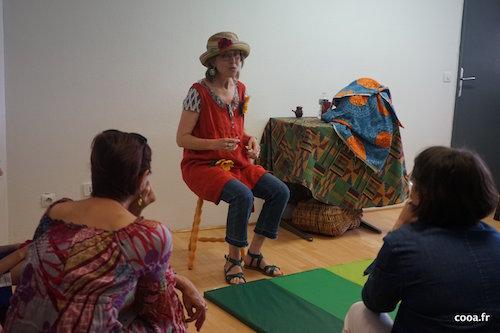 Photo prise lors des Rencontres. Virginie Loth assisse sur un tabouret, chapeau de paille sur la tête, tunique rouge, conte ses histoires devant son public.