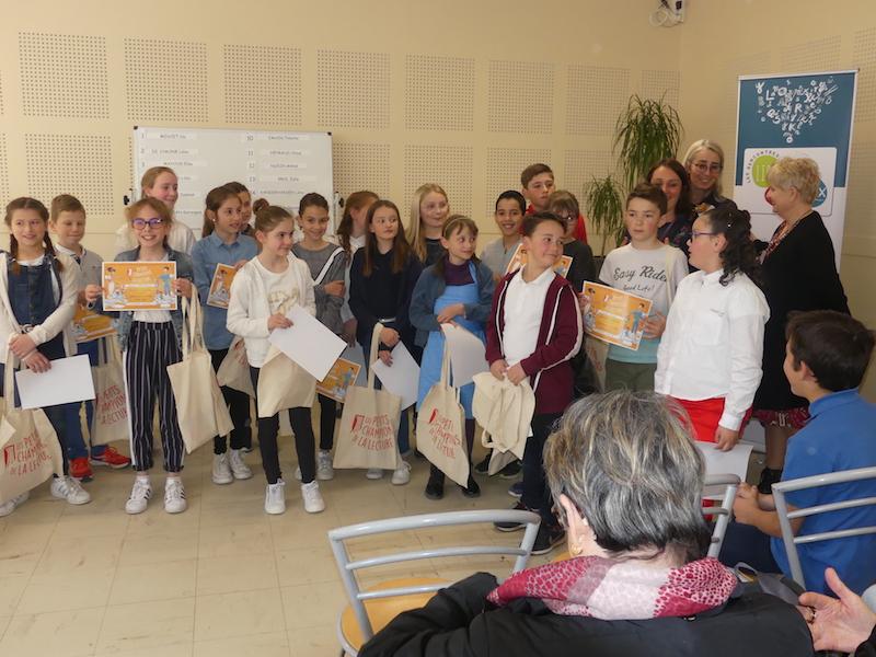 Tous les enfants participants , diplôme des Petits champions de la lecture à la main, sourient au photographe. Olivia Reny et Anny Blaise Resnik de Fréquence Lire sont avec eux.