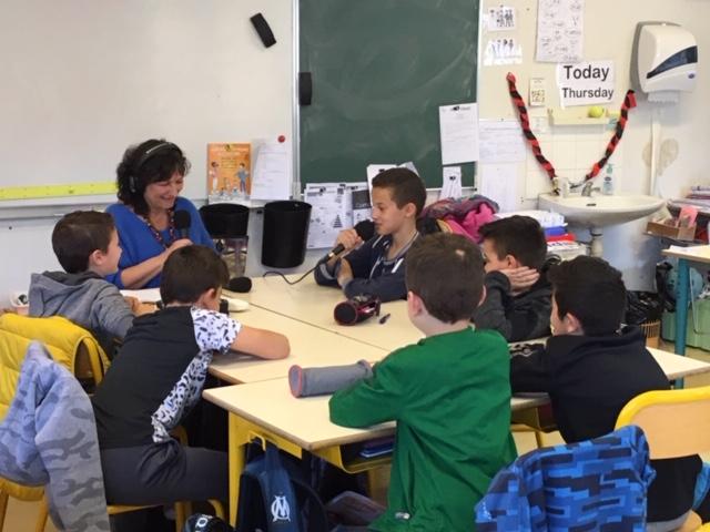 Dans une salle de classe. Autour d'une table, casque sur les oreilles, Sylvie, animatrice radio BLV, entourée de 6 jeunes garçons qui l'écoutent attentivement. Un des enfants parle au micro.