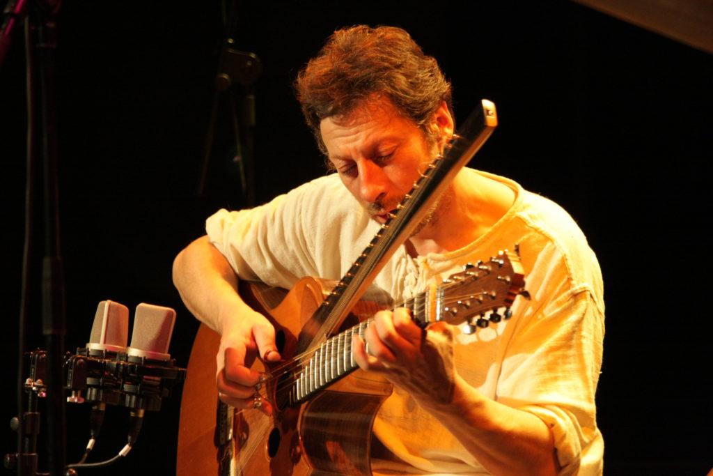 Michel Gentils jouant d'une guitare à deux manches.