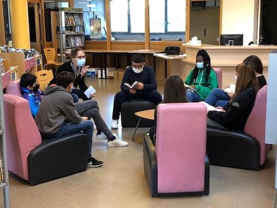 Un groupe d'élèves de cinquième assis autour d'Anne-Marie qui els écoute un par un.