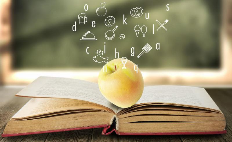 Image représentative des Mots à la bouche sur le site de Valence en Gastronomie : une pomme posée sur un livre ouvert, les lettres, et des symboles culinaires qui s'envolent : poêle, pomme, verre de bière, fouet, poisson, couverts...